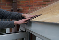 Once the plywood is fitted and secure, fit the drip tray around the edge of the roof.