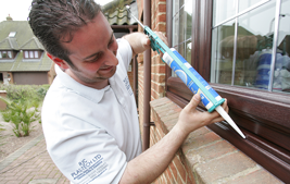 installer using silicone to install coloured upvc windows